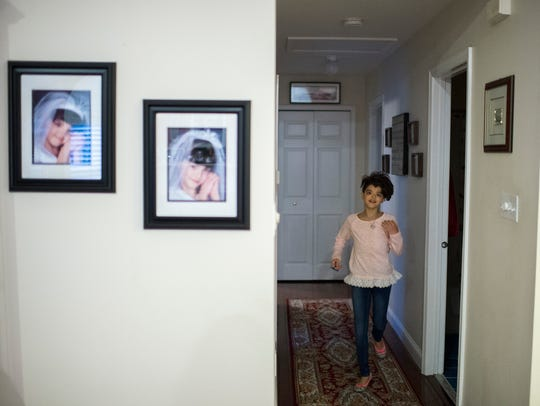 Maryelena Baldassarre, 11, runs in the hallway of her Sicklerville home. The fifth-grader was born with a facial deformity, and has endured a dozen surgeries at the Children's Hospital of Philadelphia.