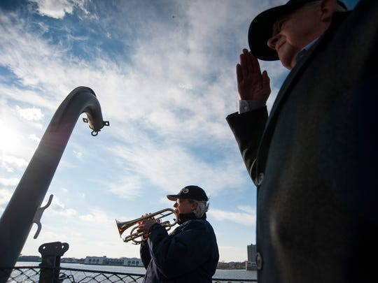 Ship bugler Nan LaCorte plays the Star Spangled Banner as a ceremony is held commemorating the 75th anniversary of the USS New Jersey's launch Thursday, Dec. 7, 2017 in Camden.