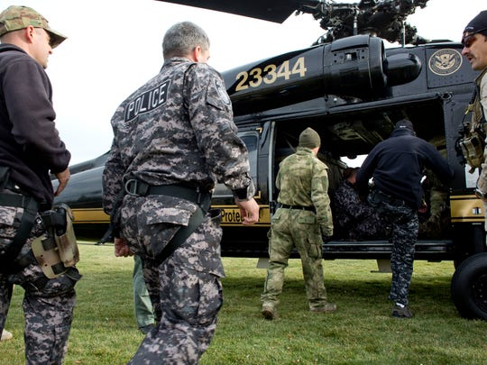 Special Response Team members from the Port Huron and Marysville police and fire departments get on a helicopter along with Customs and Border Protection officers as part of training Wednesday, November 18, 2015 at Kiefer Park in Port Huron.