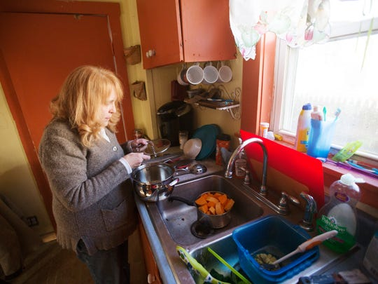 Nancy Beliveau, a resident of Pleasant Street in Auburn, Maine prepares to wash potatos as she starts making a meal. She received a lead in the drinking water notice in June but dismissed it, thinking that it affected other homes.  Her home is at least 165 years old.   Auburn was flagged for elevated lead levels in the water.  Sid Hazelton, the city's water superintendent says lead is not from the source, Lake Auburn, but comes from pipes in individual homes.