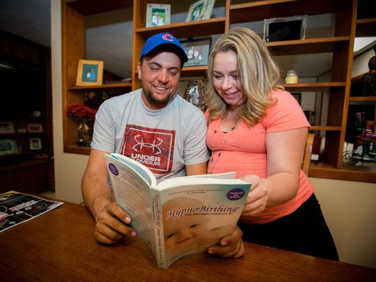 Husband and wife Casey Nowlin and Jenni Nowlin look at an instructional book on the technique of HypnoBirthing - The Mongon Method in their home, Friday, July 20, 2016.