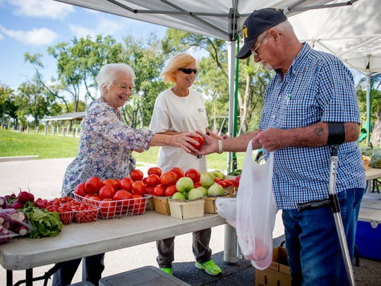 Dorothy Harrison and Darlene Brooks, of Marysville, buy produce from Tom Graf, of Marine City, at the Debbie's Veggies stand Friday, September 2, 2016 at the Marysville Farmers Market.