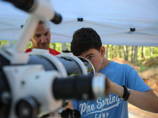 Seacrest Country Day School teacher Marc Barry, left, helps Seacrest 10th-grader Alexandre Chapelle, 15, set up a telescope Saturday, Aug. 19, 2017, in Blue Ridge, Ga. A small group of students and staff from Seacrest made the trek to Georgia to witness the solar eclipse from the path of totality.