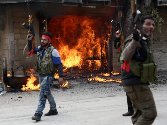 Turkish-backed Syrian rebels walk past a burning shop