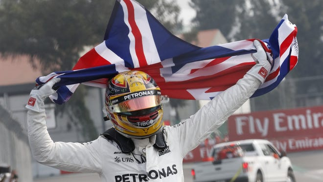 Formula One driver Lewis Hamilton celebrates after winning his fourth championship.
