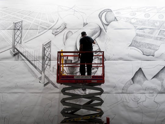 Flint artist Hubert Massey works on his mural at Cobo