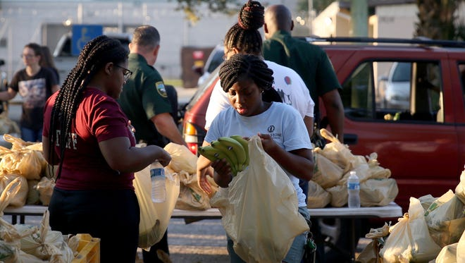 Living Stones International volunteer Tykia Maxwell (center) along with dozens of other volunteers from community organizations, LCSO, the Fire Department and EMS teamed up with Farm Share to distribute 14,000 pounds of food and toiletries at the Sheriff's offices on Municipal Way Thursday morning.