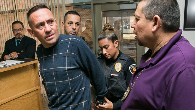 Stephen Siddall speaks with Las Cruces Police Department Detective Robert Campos, right, while being handcuffed and arrested by LCPD officer Veronica De La O and Doña Ana County Sheriff's Department Sgt. Sam Ramos on Monday in 3rd Judicial District Court  on charges of embezzlement. In the moments prior to the arrest, Siddall was in court before Judge Mary W. Rosner for an arraignment in a separate case involving credit card fraud.