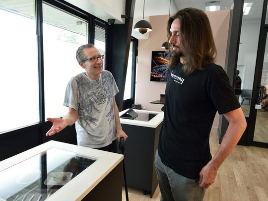 Alan Schwartz of Pompton Lakes, left, speaks with dispensary technician Niko Gallina about the strains of cannabis available at the Harmony Dispensary in Secaucus, Monday, June 18, 2018.