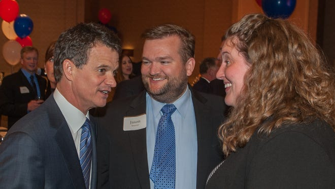 Dave Trott, left, candidate for Michigan's 11th congressional district, talks with Jason Seaver of Ferndale and Christine Rodemeyer of Livonia at his election party held at Suburban Collection Showcase in Novi Tuesday night.