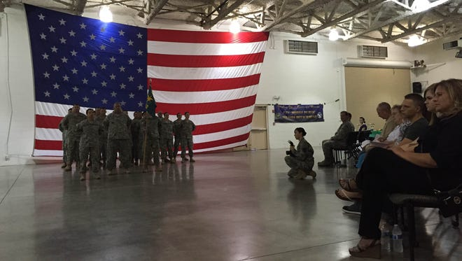 Soldiers in the 123rd Mobile Public Affairs Detachment stand in formation in front of a crowd of family members and military officials.
