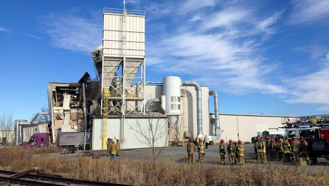 Firefighters stand outside the International Nutrition plant in Omaha, where a fire and explosion took place Jan. 20, 2014.