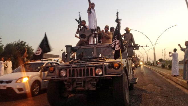 Fighters from the ISIS parade in a commandeered Iraqi security forces armored vehicle down a main road at the northern city of Mosul, Iraq.