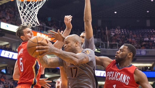 Suns forward P.J. Tucker works for a shot as the Pelicans's defense swarms him at US Airways Center in Phoenix on Thursday, March 19, 2015.