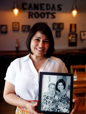 Patty Caneda holds a photo of her grandmother, Mercedes Velo,  inside her Cuban restaurant in Toms River.