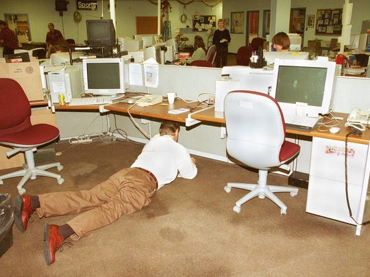 With all the noise in the newsroom due to the refurnishing, Gerald Ensley finds it easier to conduct a telephone interview from under a desk.