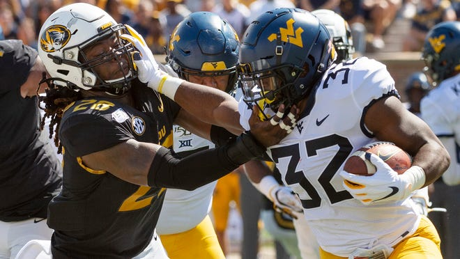 West Virginia running back Martell Pettaway, right, stiff arms Missouri defensive lineman Jatorian Hansford, left, as he runs the ball during the first half of an NCAA college football game Saturday, Sept. 7, 2019, in Columbia, Mo. (AP Photo/L.G. Patterson)