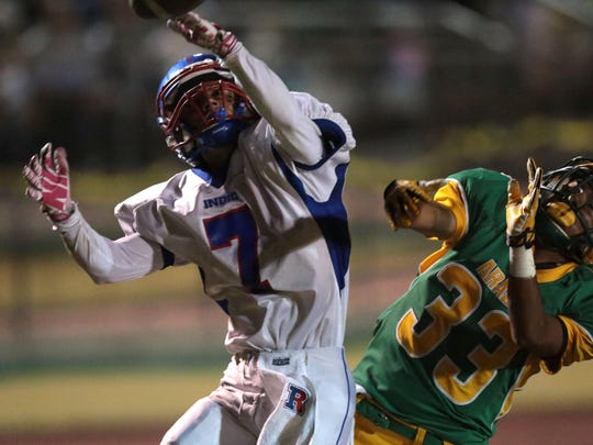 Coachella Valley's Josue Sustaita breaks up a pass intended for Indio's Fernando Meza during the annual battle for the Bell rivalry game on Friday, November 7, 2014 in Thermal.