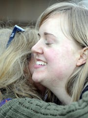 Sarah Pharis smiles as she is hugged by a friend at