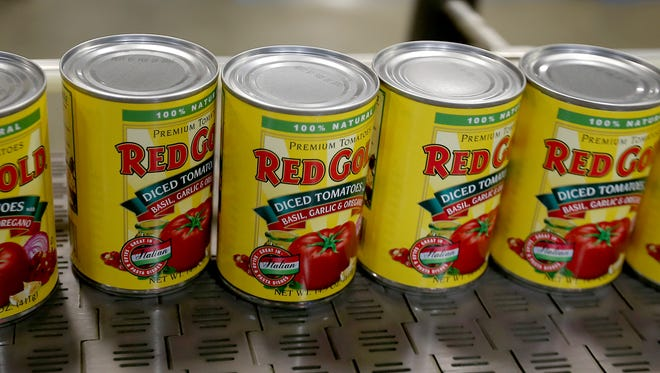 From field to can in one day, cans of Red Gold diced tomatoes roll off the line Oct. 2, 2014, at the canning facility in Orestes, Indiana.