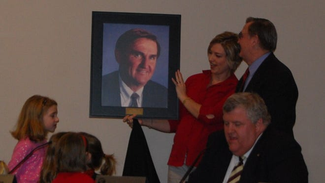 Erlanger City Attorney Frank Wichmann is presented with a portrait in 2009 to hang in a conference room named for him by council in the city building.