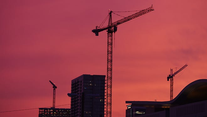 Construction cranes in downtown Nashville skyline during sunset on July 15, 2015.