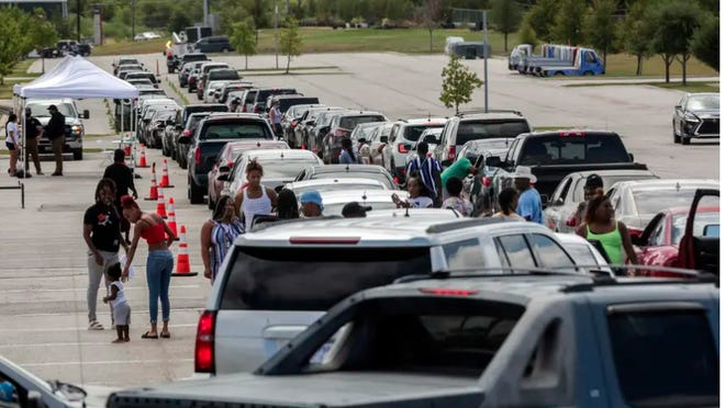 Hundreds of Hurricane Laura evacuees wait in their cars as they line up for hotel vouchers at the Circuit of the Americas in Austin.