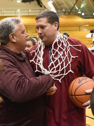 After securing the net from the regional championship at Otterbein, Newark coach J.R. Shumate receives congratulations from superintendent Doug Ute.
