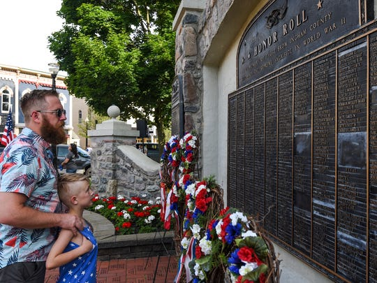 Forrest Page, and son Gibson, 7, of Mason, read names