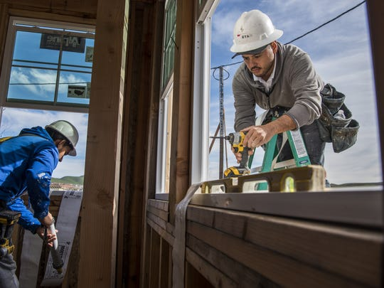 Contractors install a window on a home.