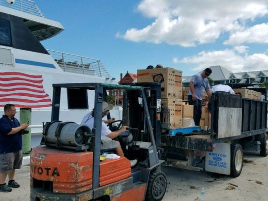 Off-duty Cape Coral firefighters volunteer and unload supplies from the Key West Express boat in Key West after Hurricane Irma.