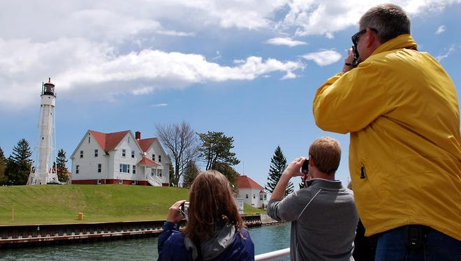 The Sturgeon Bay Canal Light, operated by the US Coast Guard, gets attention from photographers aboard a Sturgeon Bay Fireboat Cruise during the Door County Lighthouse Festival.