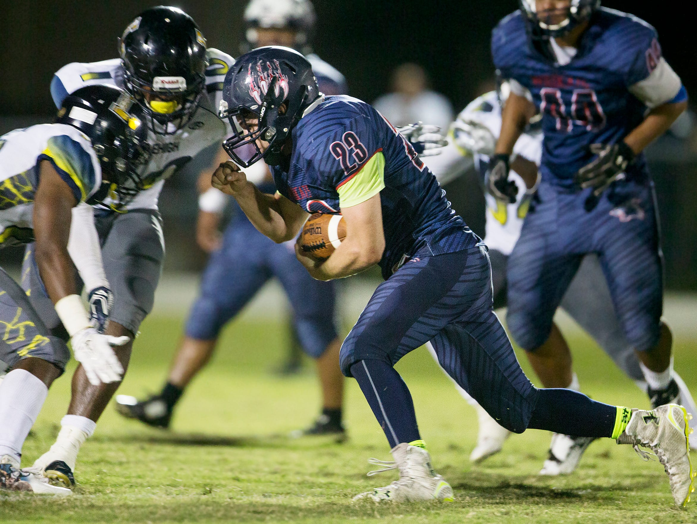 Estero High School's Jonathan Rauss takes on Lehigh defenders during second quarter play on Friday at Estero High School.