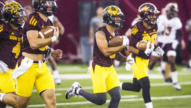 Arizona State University players run with the ball at practice at the Dickey Dome on campus, Wednesday, August 5, 2015.  From left to right are; Josh Pokraka, D.J. Foster and Daniel Groebner.