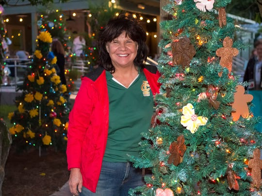 Standing with one of the decorated trees is Linda Meyer