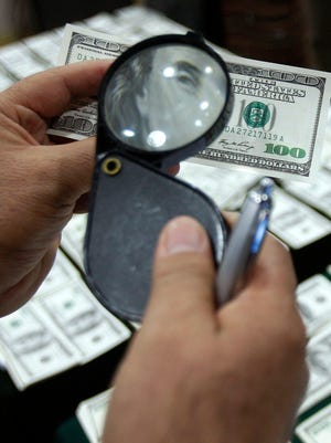 A police officer inspects an alleged counterfeit 100 dollar bill in this file photo.
