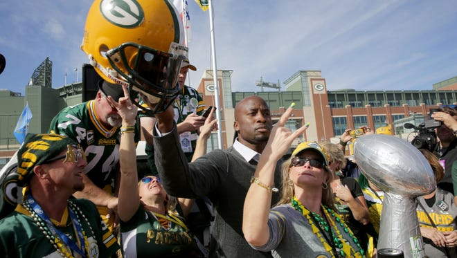 Akbar Gbaja-Biamila, center, a sports analyst for the NFL Network and younger brother of former Green Bay Packer Kabeer Gbaja-Biamila, dances with fans before before the Green Bay Packers game against the Dallas Cowboys at Lambeau Field in Green Bay, Wis. on Sunday, October 16, 2016.