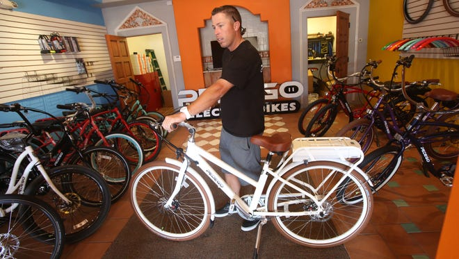 Bryan Newman, owner and operator of the Pedego bike shop in La Quinta, shows off one of his electric assist bikes. He also operates a store in downtown Palm Springs. Both offer special, themed tours for individuals or groups.