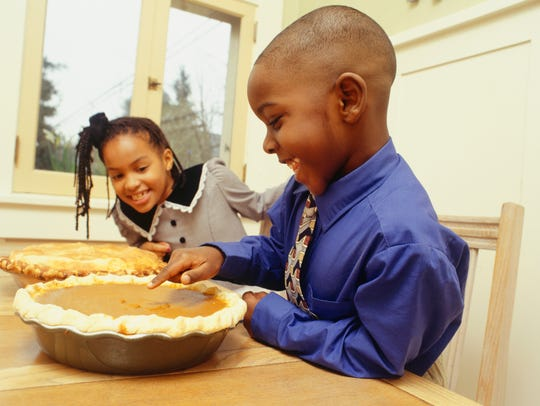 A little girl watches a boy stick his finger in a pie.