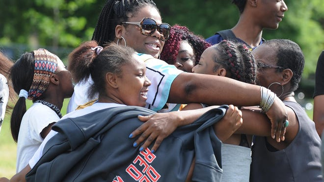 Denby Principal Tanisha Manningham, center, is mobbed by students and well-wishers as Life Remodeled CEO Chris Lambert calls out for them to show some love to those involved in making the project happen.