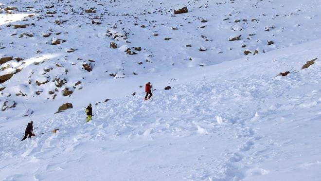 """In this Monday, Oct. 9, 2017, photo provided by the The Gallatin National Forest Avalanche Center, searchers probe the lower portion of an avalanche debris field for a missing skier on Imp Peak in the southern Madison Range in southwestern Montana. The body of Inge Perkins was recovered after two skiers triggered the weekend avalanche that fully buried Perkins and partially buried renowned mountaineer Hayden Kennedy. After losing his girlfriend in the avalanche, Kennedy """"chose to end his life"""" the following day, his family said Tuesday."""
