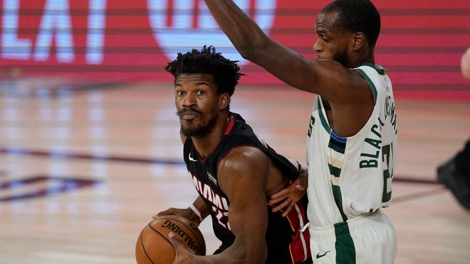 Miami Heat's Jimmy Butler, left, drives against Milwaukee Bucks' Khris Middleton (22) in the first half of an NBA conference semifinal playoff basketball game Tuesday, Sept. 8, 2020 in Lake Buena Vista, Fla.