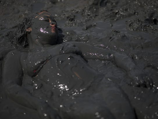 A mud covered woman lays in the mud during the traditional