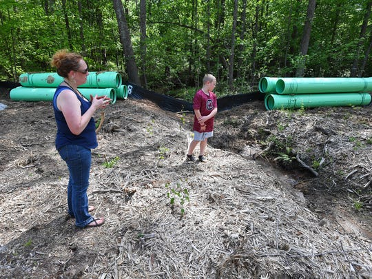 Jonelle Phillips and her son Seth look over newly laid sewer lines being laid behind their home on Phillips McCall Road in Greer Thursday, May 3, 2018. Phillips is concerned about a new 180 home subdivision proposed for next door that is taking advantage the sewer lines.