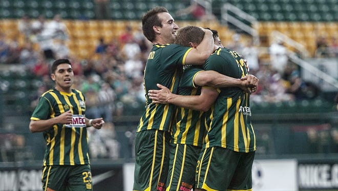 Rochester's Tyler Rosenlund and Matt Garzi, center, hug Colin Rolfe, right, after the Rhinos' first-half goal against D.C. United Tuesday.