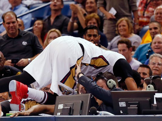 New Orleans Pelicans forward Anthony Davis is helped after falling onto the scorers table in the first half of an NBA basketball game against the Dallas Mavericks in New Orleans, Wednesday, March 29, 2017. (AP Photo/Gerald Herbert)