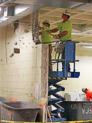 Construction workers bring down a wall, as part of