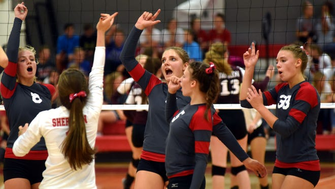 Members of Sheridan's volleyball team celebrate after winning a point during a match against John Glenn last Monday at Glen Hursey Gymnasium.