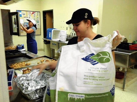 Allouette Hummer packs up lunches of fish nuggets and fries at the Boys and Girls Club for the Summer Food Program.
