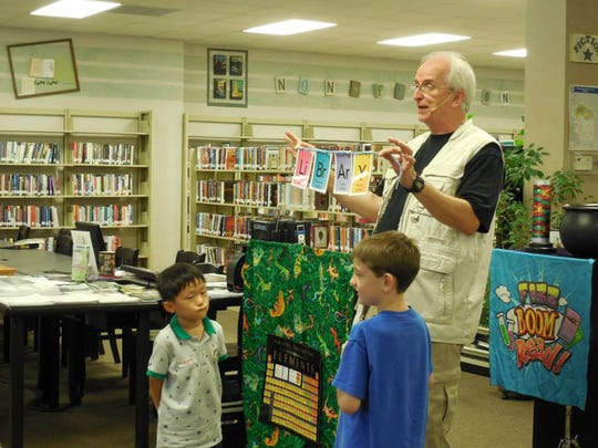 Magician and puppeteer Tommy Johns and two assistants perform a trick for the audience. He will be appearing on June 7 at the Pike Road library.